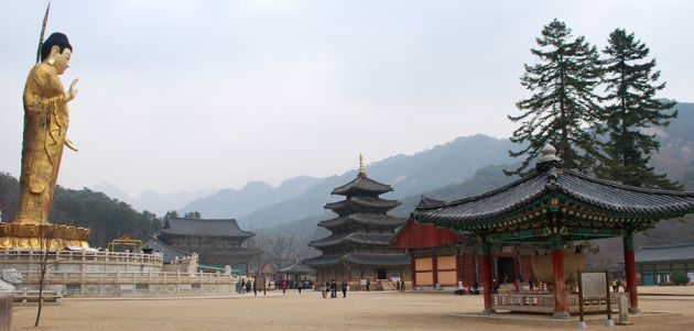 The Beopjusa Buddhist Temple with ancient buildings including a bell pavilion, a large pagoda pavilion, and a large golden Buddha statue.