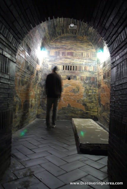 The blurry outline of a man inside one of the Songsanri Tombs. The interior features ancient bricks set in a barrel vault with a raised stone platform for burial.