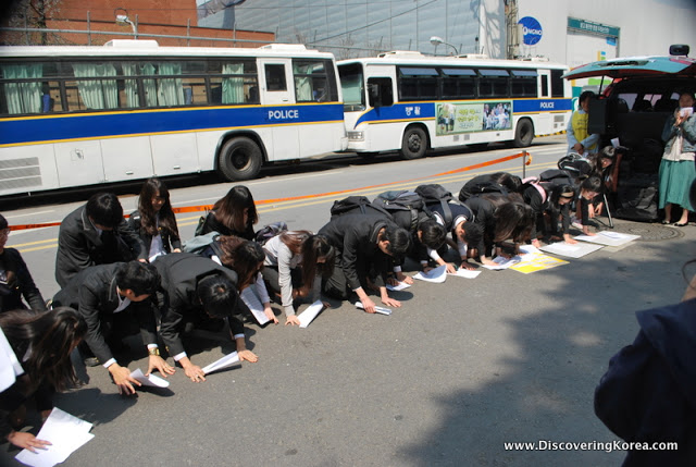 Korean school children kneeling on their hands and knees paying customary respect to the elder former comfort women.