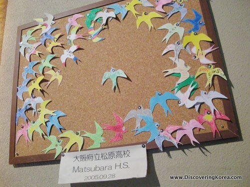 Paper birds made by Japanese school children and given to former Korean comfort women as a show of solidarity. They paper birds are pinned to a cork boarded.