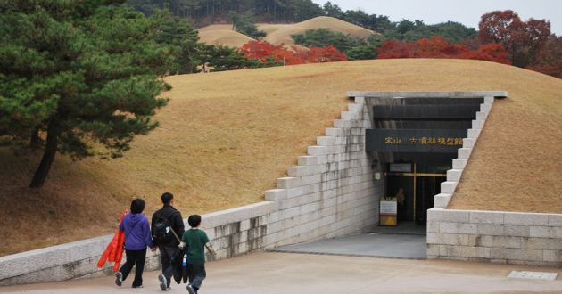 A small family of Korean walk into an earthen mound that contains the entranc to one of the Songsanri Tombs of Gongju Korea.