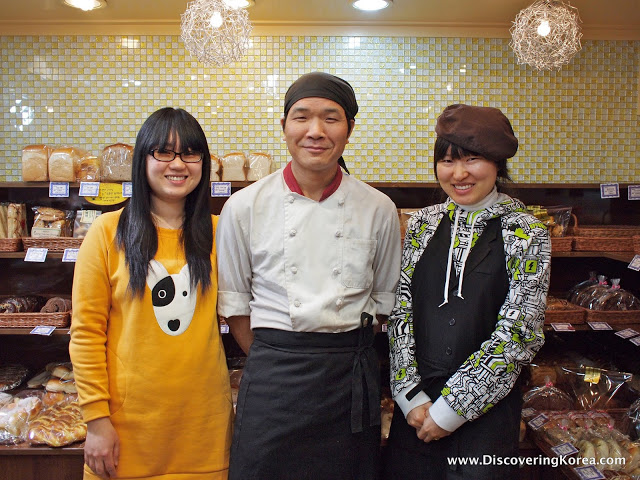Three people standing in a bakery with bread and pastries in the background. The woman on the right is wearing a yellow dress, the man in the middle is wearing a white chef's coat and black apron, and the woman on the right in a black and white shirt with a black apron.