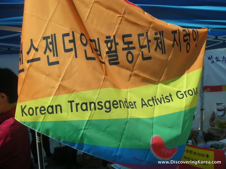 An orange, yellow, green, and blue flag with black Korean lettering and text on it.