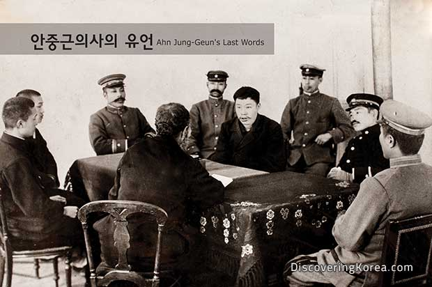 An old sepia photo of Ahn Jun-Geun addressing army officers around a table with a dark cloth.