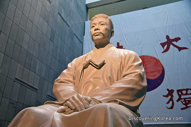 A statue of Ahn Jung in light stone, on a backdrop of a stone wall and a fabric hanging with a red and blue yin-yang sign and Korean lettering.