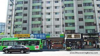 A grey and green high rise apartment block in Yongsan, with shopfronts at street level, and traffic on the road in front.