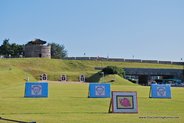 A green field with archery targets, in bright sunshine at Suwon Hwaseong fortress.