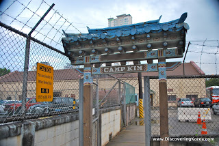 """A gate flanked in wire fencing and barbed wire. An ornate roof over the small entranceway with words """"Camp Kim"""" printed above."""