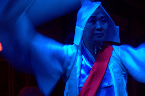 Close up of a woman with traditional robes and headwear, with a red sash dancing, in a blue light on a black background.
