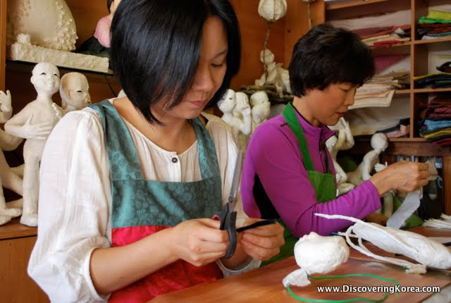 Two ladies at Jeonju hanok village sewing in a fabric shop with dolls in the background.