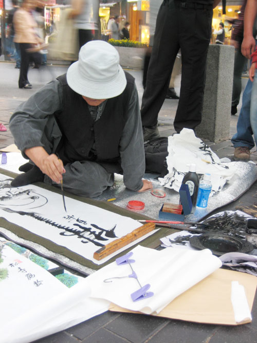 A man sits on the sidewalk, painting a picture on a white paper, with various art supplies around him.