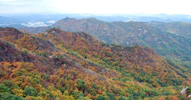 Looking down over rolling hills, covered in forests with fall colors in Korea.