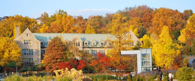 A large stone house with light green roof nestled amongst trees with their yellow, red, and orange autumnal leaves.
