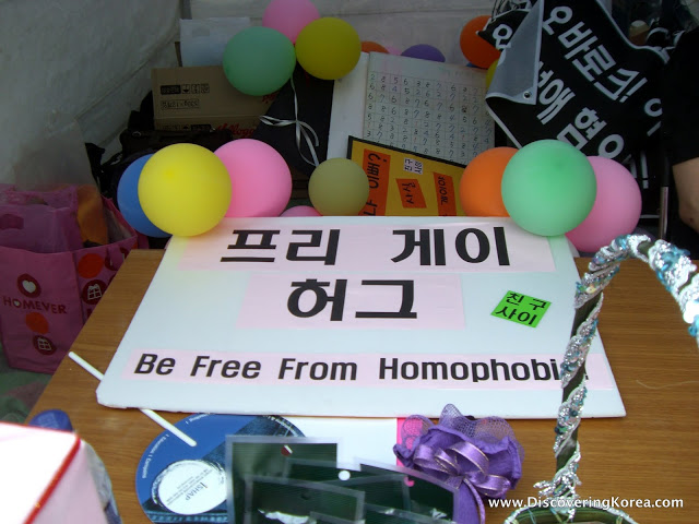 A messy room with balloons, paperwork, boxes and banners. A white placard with black writing is in the center of the frame on a wooden table.