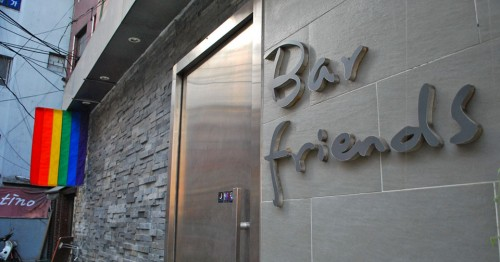 The entrance to a bar with a sign on the right of the frame saying Bar Friends on stone, a metal door and slate wall, with a rainbow flag hanging from the eaves to the left of the frame.