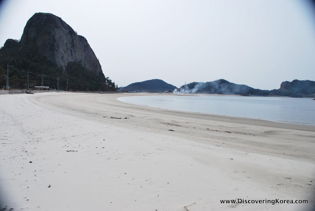 A deserted white sand beach at Seonyudo, with black rock mountains in the background, on a cloudy day.