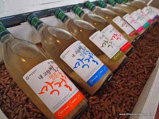 Bottles of rice beer lying next to each other on wooden pellets, close up.
