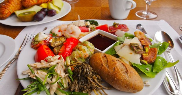 A white plate with various different food, a bread roll, some shrimp, some chicken and soy sauce in a smaller bowl in the center, in the background is a plate with croissant and fruit, on a white place mat on a wooden table.