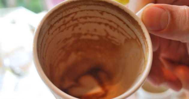 Close up of a white cup emptied of coffee with a small heart shape in the bottom made from frothy milk and chocolate powder.