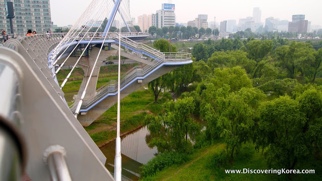 To the left shows a bridge crossing a river, with the city in the background and trees to the right of the frame.