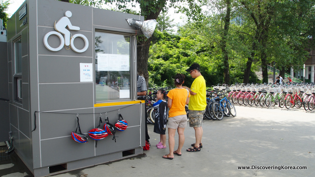 A grey bicycle rental office with cycling helmets hanging from it, two people standing at the kiosk with rows of bicycles behind.
