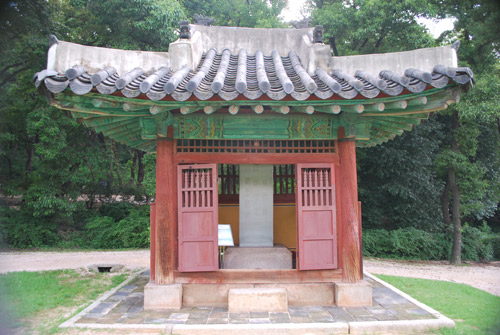 A small wooden house in deep red, with turquoise eaves and a traditional curved roof, surrounded by a stone plinth. Through the open door a concrete block. Pine forest in the background.
