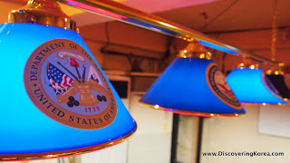 Close up of blue lampshades with United States emblems on them, lit up.