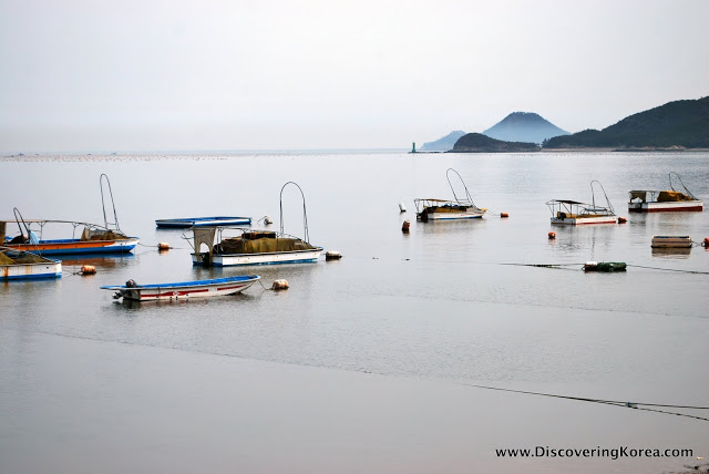 A view over the harbor at Seonyudo island, with boats moored in calm waters, with mountains in the background in soft light.