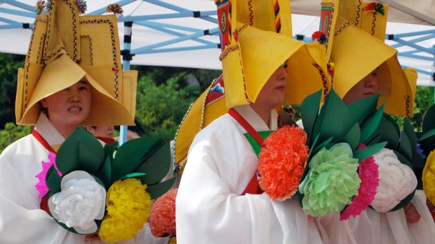 Three women in long, white robes with pagoda-shaped hats holding orange, green, yellow and pink flowers at the Bongwosa Buddhist temple, taking part in Yeongsanjae ceremony.