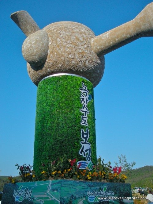 A stone statue, with a circular top, with plants growing around the base at Boseong tea plantation.