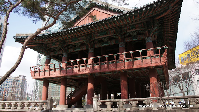 A large wooden building with traditional curved roof, a balcony, and ornate wood carvings in the eaves, the Bosingak belfry in Seoul.
