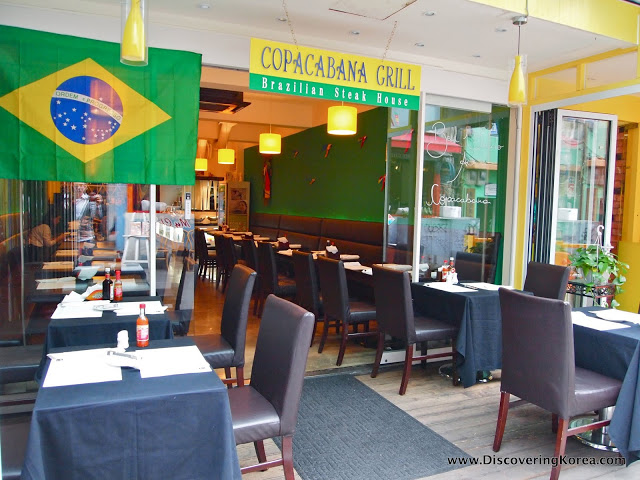 Looking into a Brazilian restaurant, with outside tables, dark brown chairs, dark blue tablecloths. Through the glass doors is more seating, with green walls and yellow lighting.