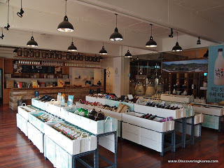 Shop display of bottles of rice beer, in white rows, with a cafe counter behind and lights hanging from the ceiling. The floor is hardwood.