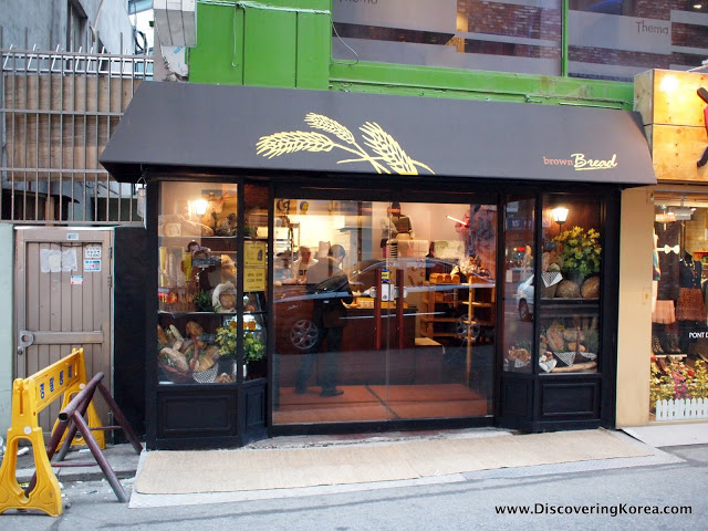 A street entrance to a bakery in Seoul, shopfront with glass doors and dark colored awning and surround.