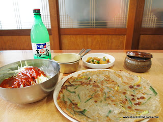 A table set with a dish of buckwheat pancakes, a noodle dish with a red sauce in a metal bowl, condiments behind and bottle of rice wine.
