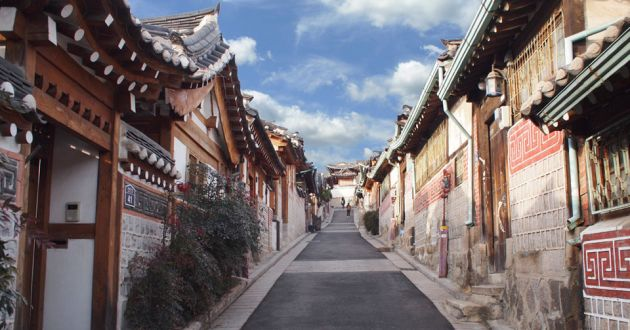 A narrow street in Bukchon Hanok Village with wooden buildings on either side, decorated with red and white tile work. Blue sky and clouds in the background.