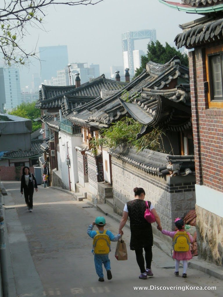A mom walks her brightly-clad, school-bound kids down an alley in Seoul's historic Bukchon neighborhood. The modern Samseong Tower is in the distance.
