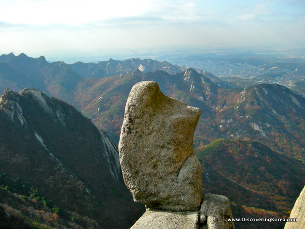 A rock formation in the foreground, with mountains overlooking Seoul in the background.