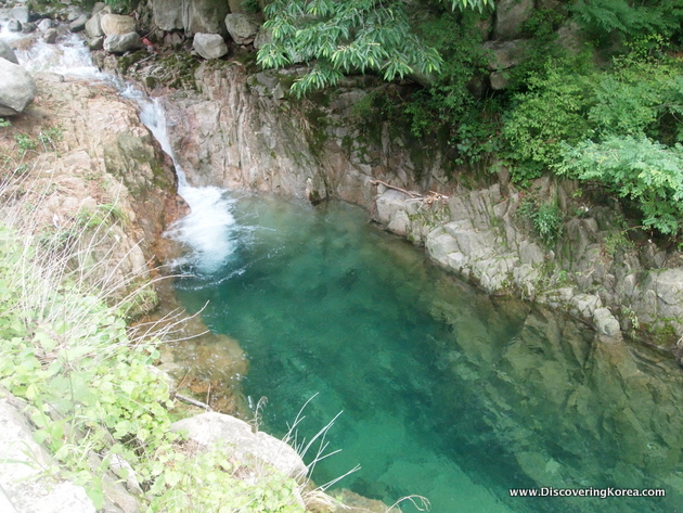 A waterfall from the right of the frame empties into a crystal clear pool of water in a gully, cut out of the rocks in Bukhansan national park.