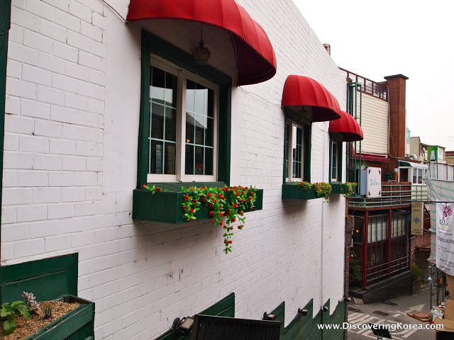The side of a white brick building, with green painted windows, and trailing plants from the windowboxes. Above the windows are red shade overhangs, at Seoul's only Bulgarian restaurant.