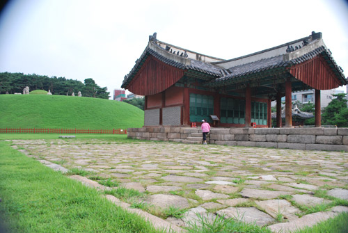 A wooden building with a traditional curved roof, with a stone courtyard surrounded by grass, the burial site of King Seongjong.