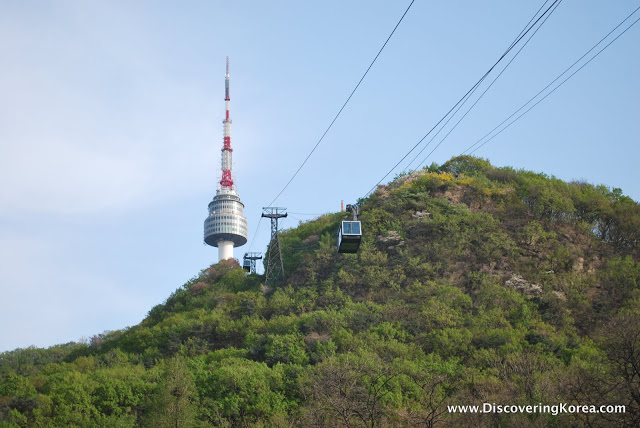 Cable cars going up a mountain to N Seoul tower, the red and white spire and observatory can be seen to the left of the image. A blue sky background.