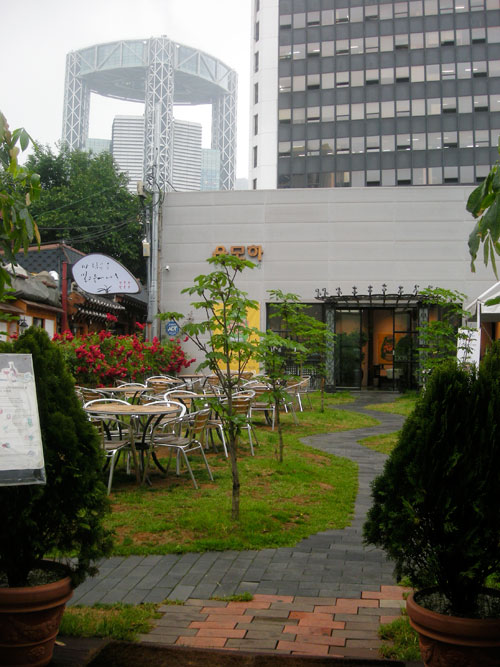 The outside seating area of a cafe, with chairs and tables to the left of the frame, a sunflower and a paved walkway into a large building, with a metal structure in the background.
