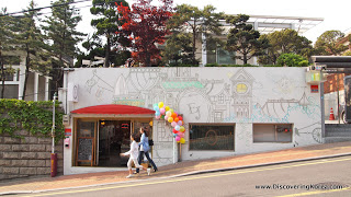 Two people walking downhill on a street, outside a quirky cafe, with murals on the white walls. In the background are trees.