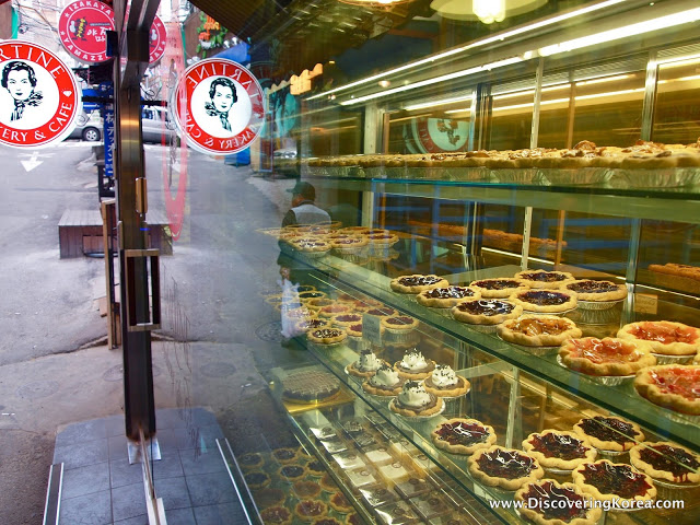 A cafe display cabinet showing various different cakes and tarts, on glass shelves. To the right of the frame is the cafe door leading to the street.