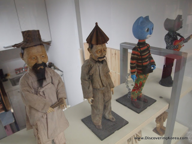 Wood carvings in a glass cabinet on display. Two Korean men in traditional hats and gray robes, and a figure with a blue cat's head wearing a multicolored sweater and pants.
