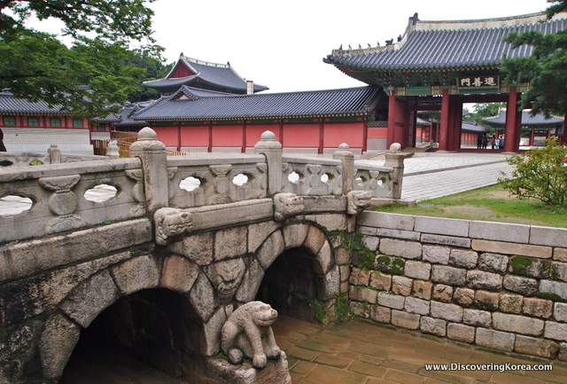 Changdeokgung bridge, a stone structure, with a mythical creature carved out of stone, and arches to let the water flow. The background is the entrance to the palace, an ornate building in red, with a dark roof.