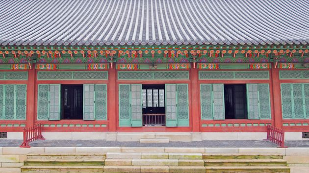 Outside view of Changdeokgung Palace, showing red pillars, with turquoise fretwork on the windows, ornate design in the eaves, and stone steps up to the doors.