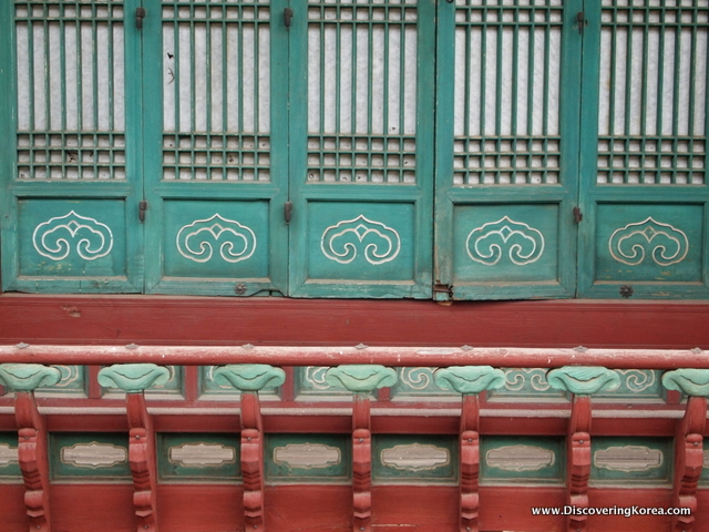 Close up of Changdeokgung Palace window shutters, carved wood in turquoise above, and deep red color below.