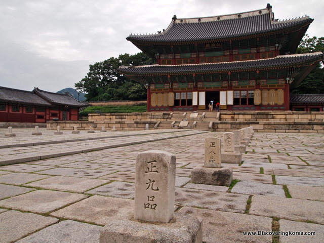 External view of a stone terrace, with headstones approaching the steps to Changdeokgung Palace, an ornate building in red and turquoise with a dark roof.